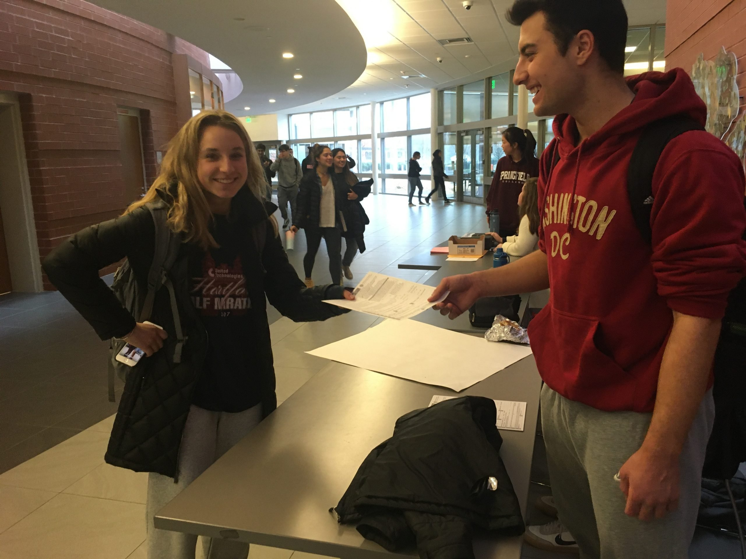 Junior Hannah Adams accepts a voting registration sheet from Thomas Coulouras at lunch.